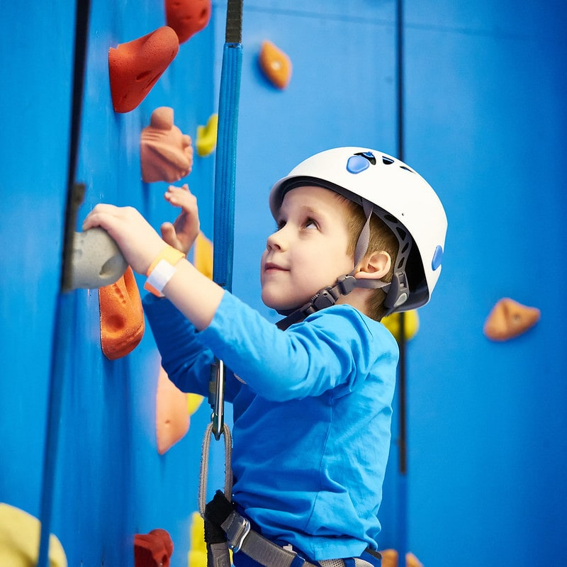 Little boy scaling a blue climbing wall.