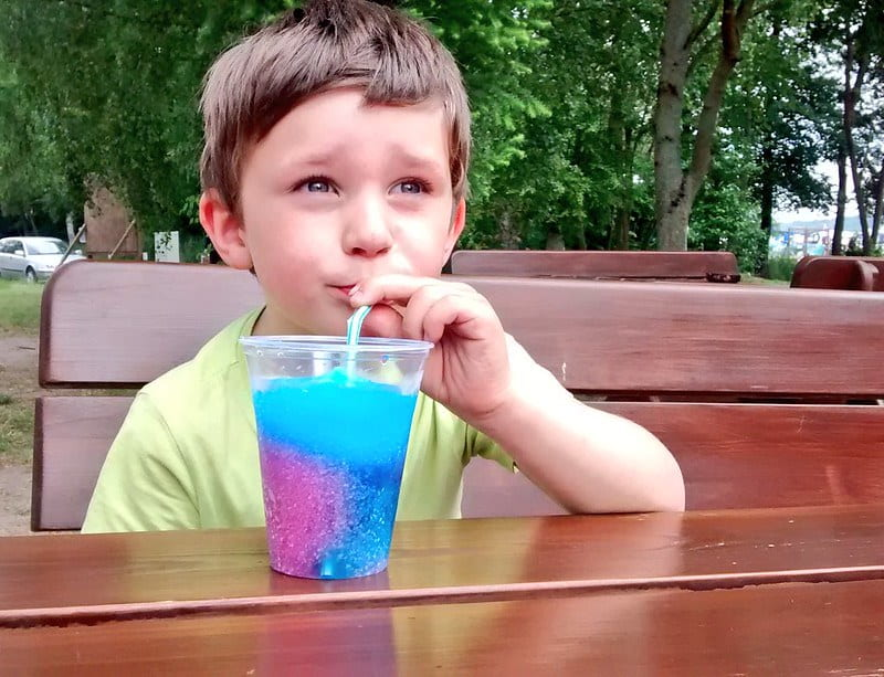 Boy sat outside drinking a red and blue slushy.