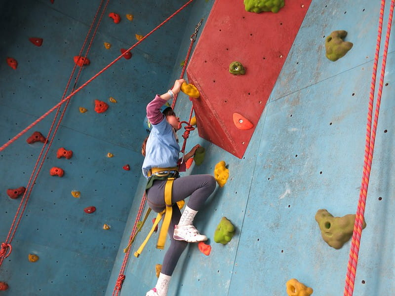 Young girl climbing a tricky part of the rock wall.