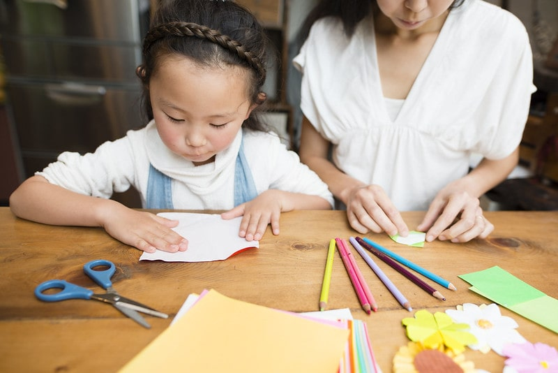 Young girl and her mum at the table cutting out paper to make dolls shoes.