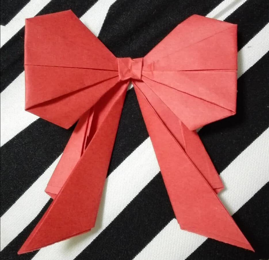 A red origami bow against a black and white striped background.