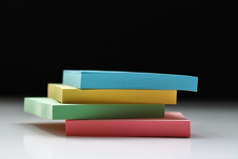 A pile of four different coloured pads of origami paper.