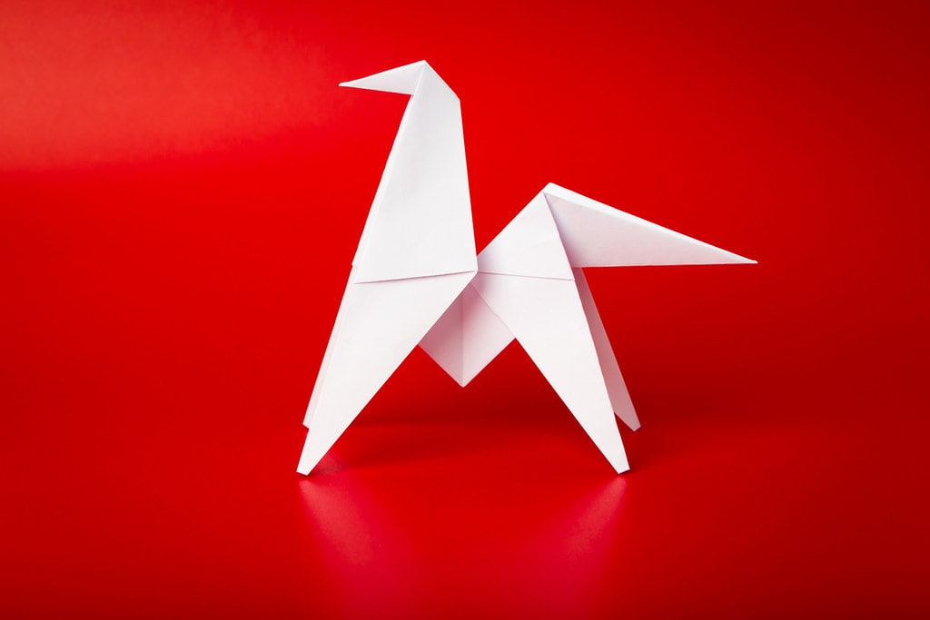White origami horse against a red background.