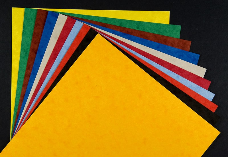 A pile of coloured, textured card fanned out against a black background.