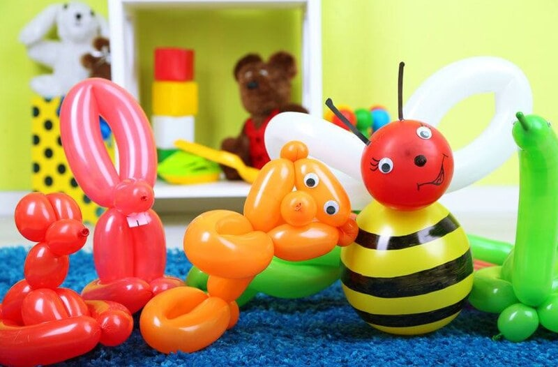 Various balloon animals, including a bee, lined up next to each other.
