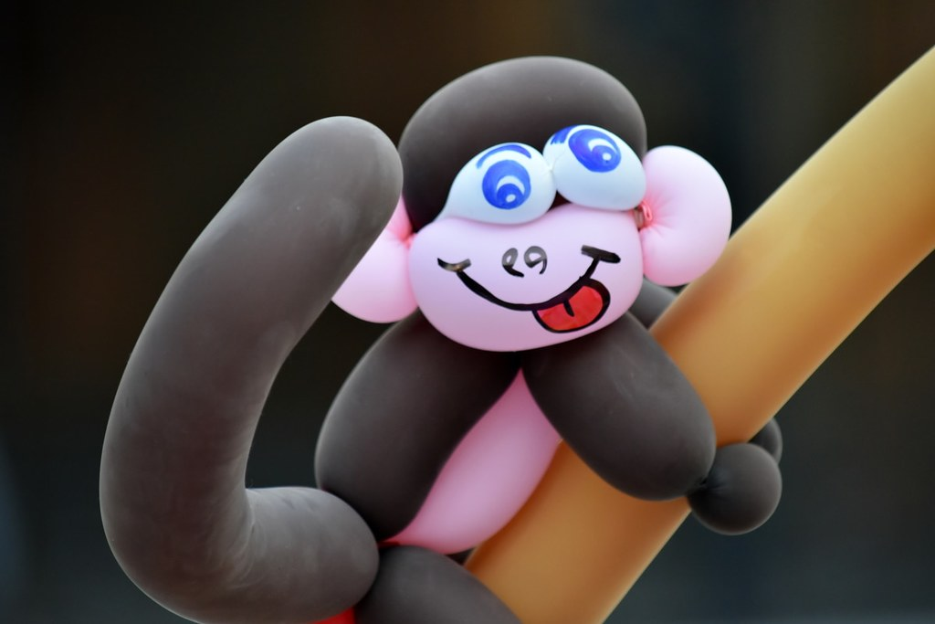 Balloon monkey made from pink and black balloons, with a silly face drawn on.