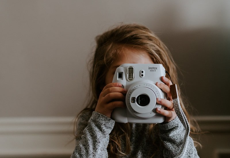 Little girl taking a photo with a polaroid camera.