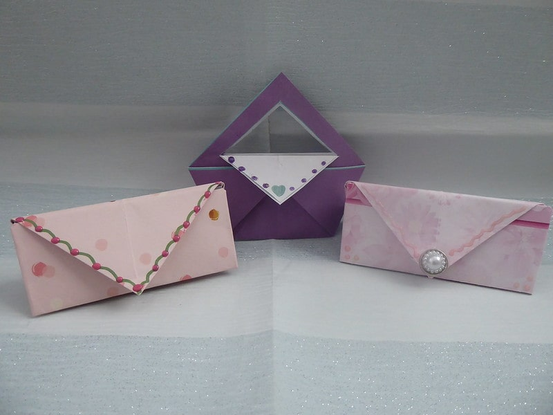 Three pretty origami purses, decorated with pearls and stickers.