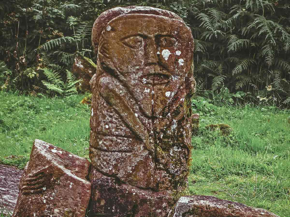 Celtic stone, resembling a tombstone, with a face engraved into it.