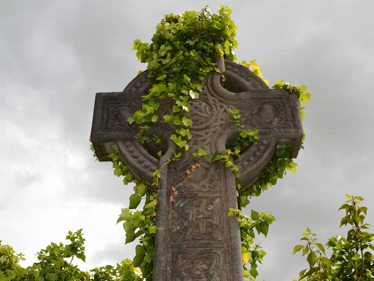 A Celtic stone monument with ivy growing over it.