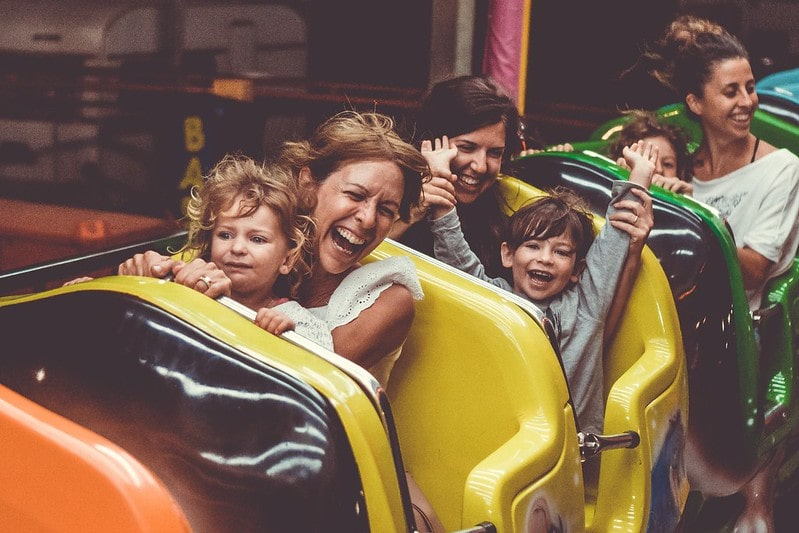 Kids and parents having fun on a rollercoaster.