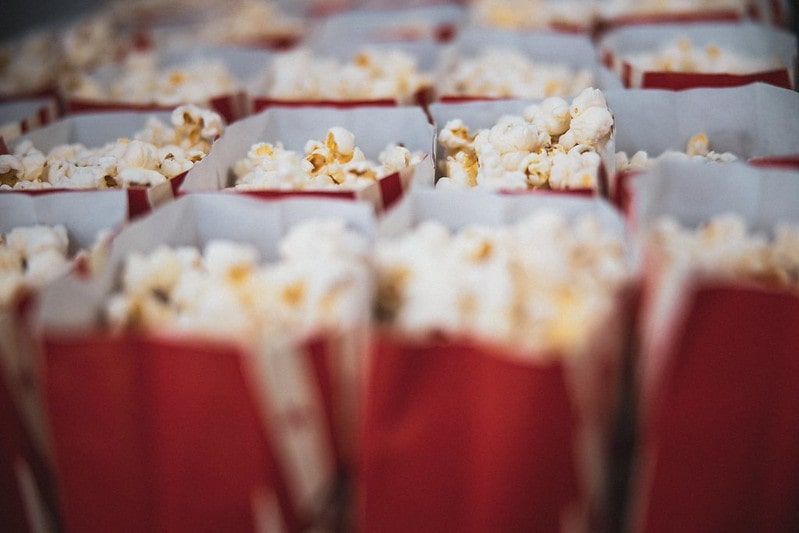 Red bags of popcorn lined up next to one another at the cinema.