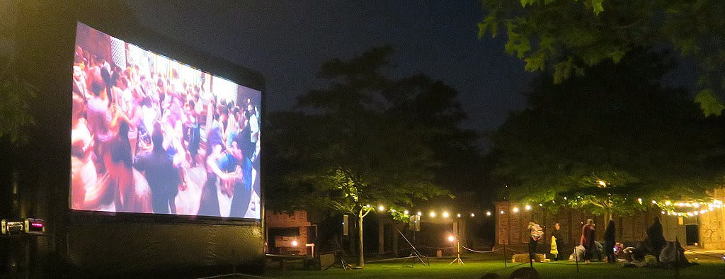 The large screen showing a ballroom scene in a movie at Moonbeamers Drive In Cinema.