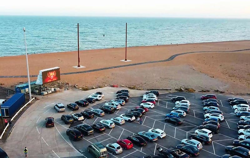 Cars parked up to watch a movie on a big screen just by the seafront.