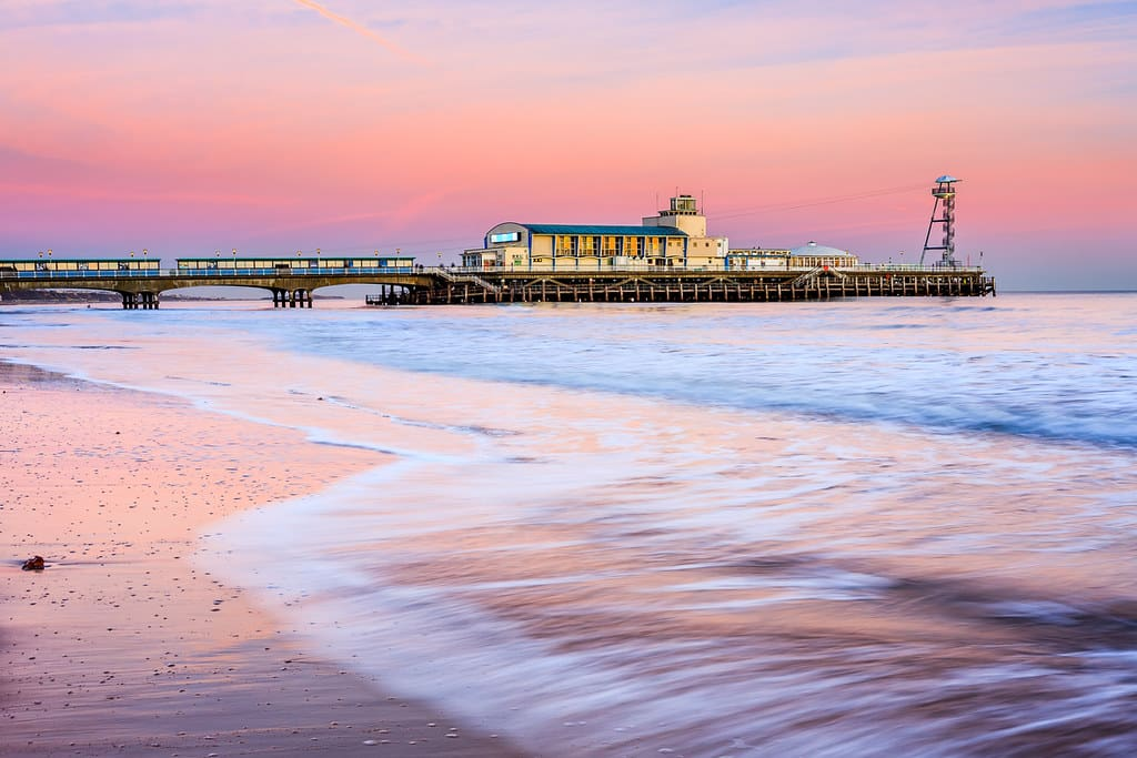Bournemouth pier at sunset, the skies pink and lilac in the background.