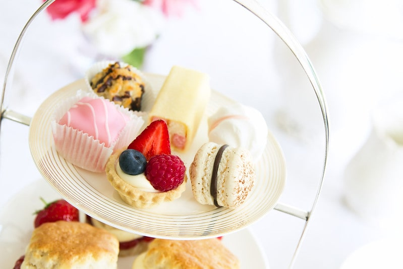 Assortment of cakes on a tiered platter at afternoon tea.
