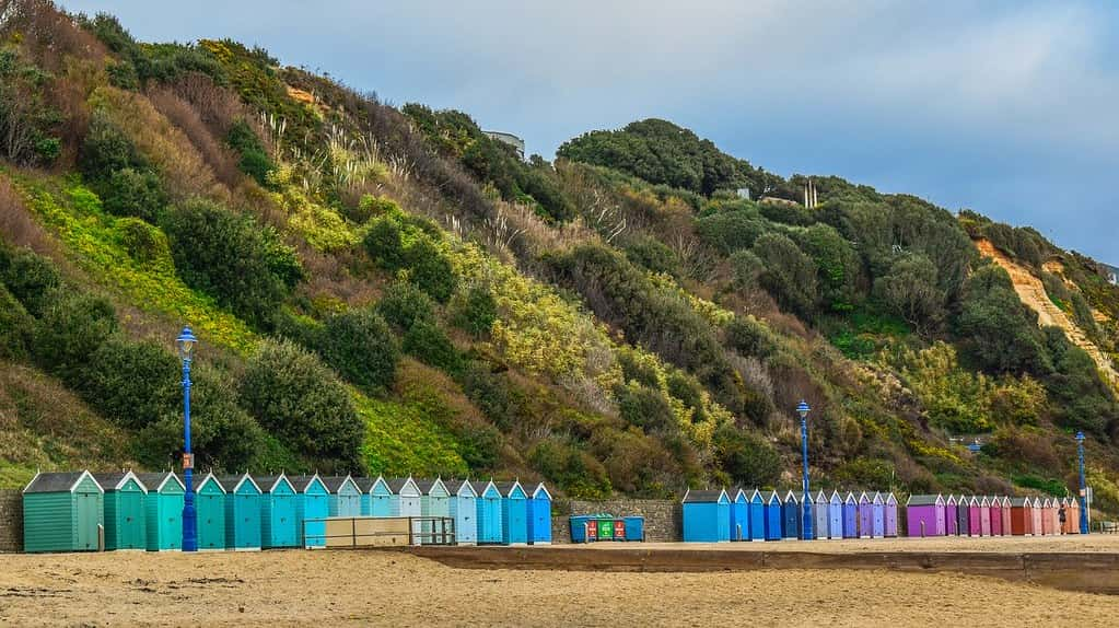 Colourful beach huts lining Bournemouth beach, with green hills behind.
