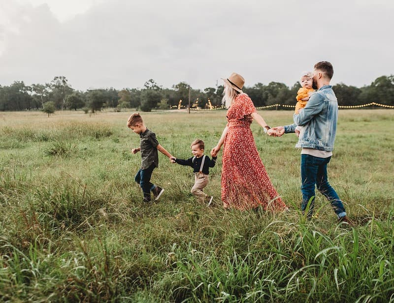 Family of five on a nature walk through the field.