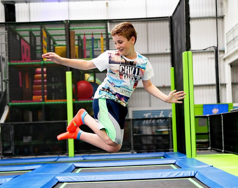 Young boy posing in the air as he bounces at Jump In trampoline park.