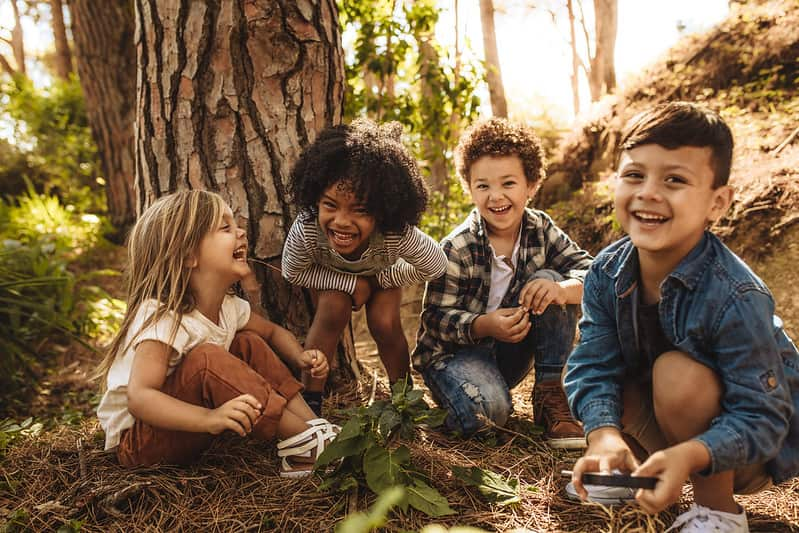 Young kids sitting in the forest next to a tree laughing at plant jokes.