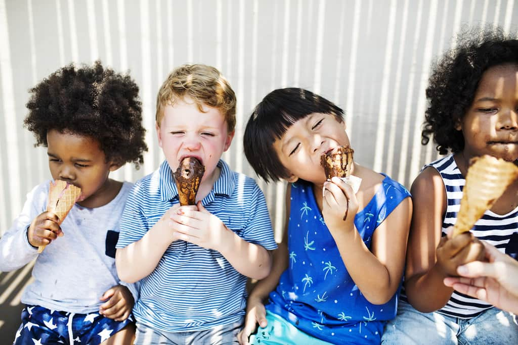 Four kids stood together licking their ice cream cones with ice cream all around their mouths.