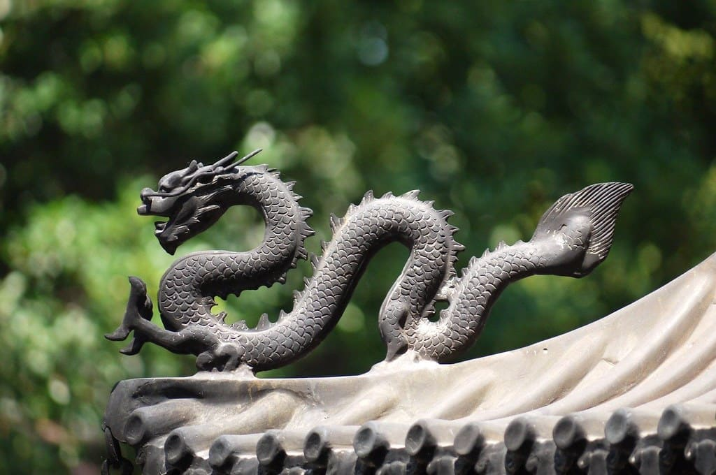 Black metal Chinese dragon statue on the corner of a building.