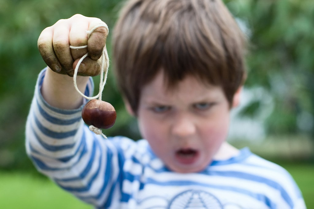 Young boy with soil all over his hands holding up a conker and making a silly face.