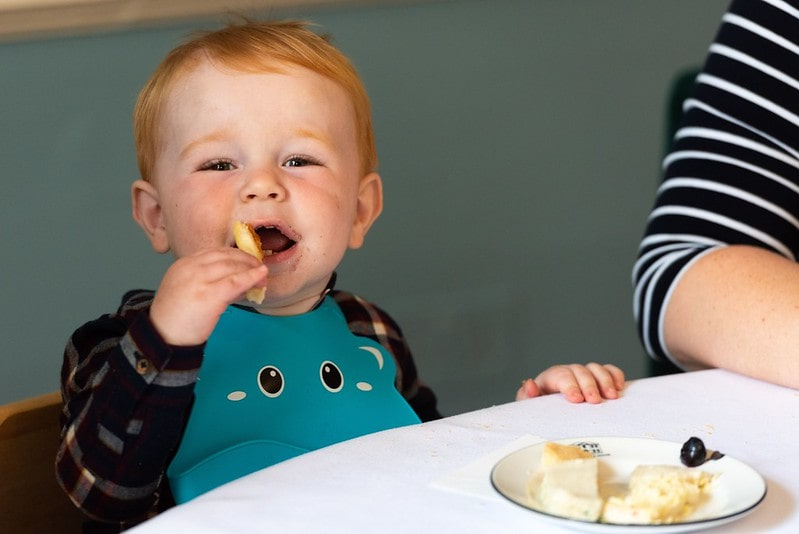 Young boy happily eating his food at afternoon tea.