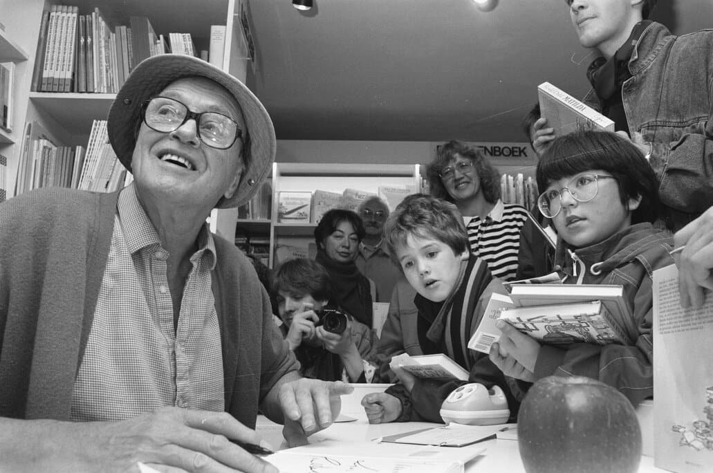 Black and white photograph of Roald Dahl signing books for children.