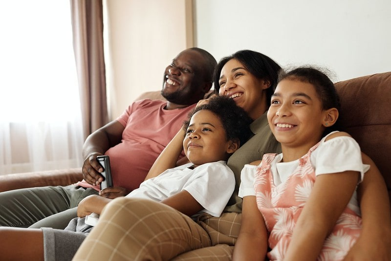 Family of four sat on the sofa together smiling and laughing at spider puns.