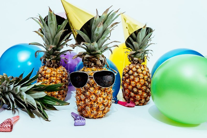 Funny pineapple party: pineapples wearing sunglasses and party hats with balloons around them.