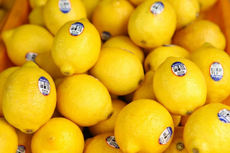 Crate of bright yellow lemons with stickers on.