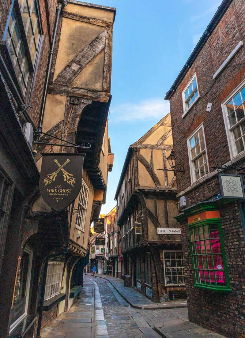 Narrow street in York's Shambles lined with shops and cafés.