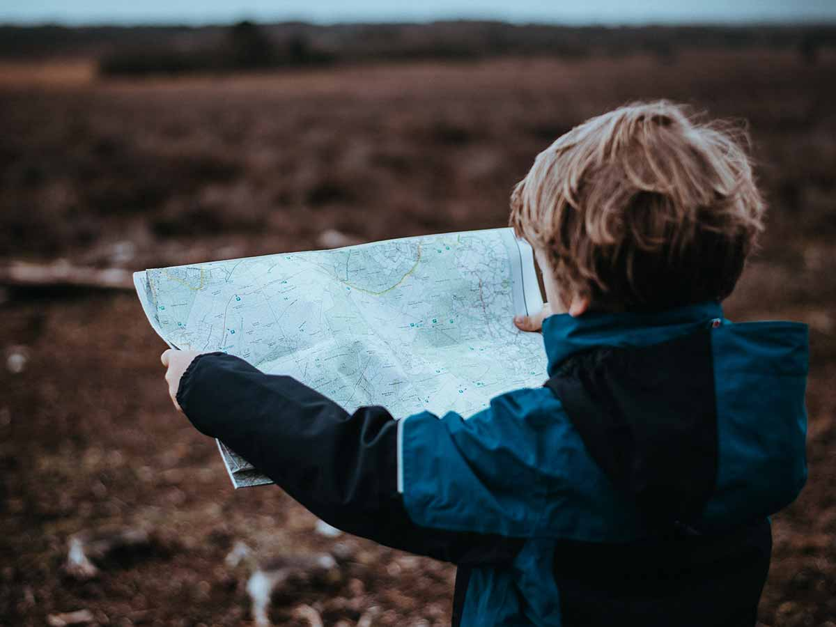 Young boy holding up a map trying to read it.