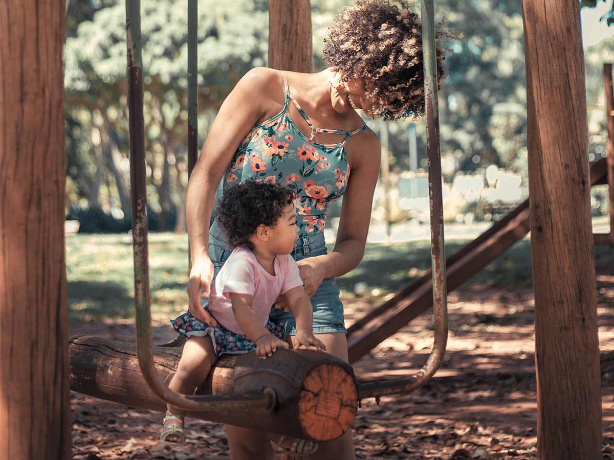 Mum supporting her child on a log swing in the park.