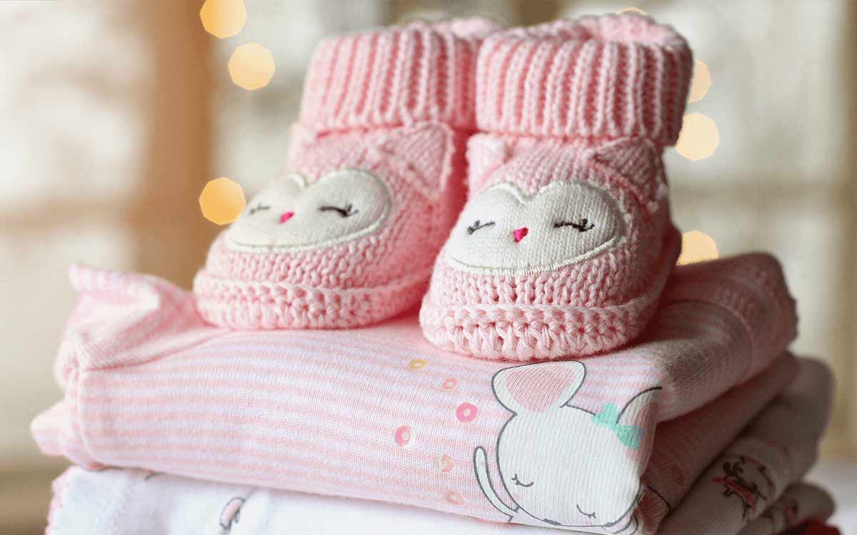 Pair of pink knitted baby boots on top of a pile of pink baby clothes.