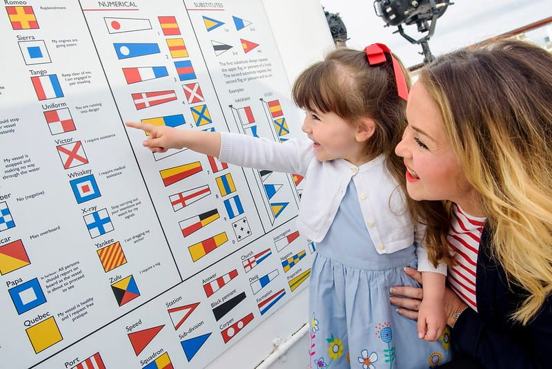 A mother and daughter looking at some boating signage on the Royal Yacht Britannia.
