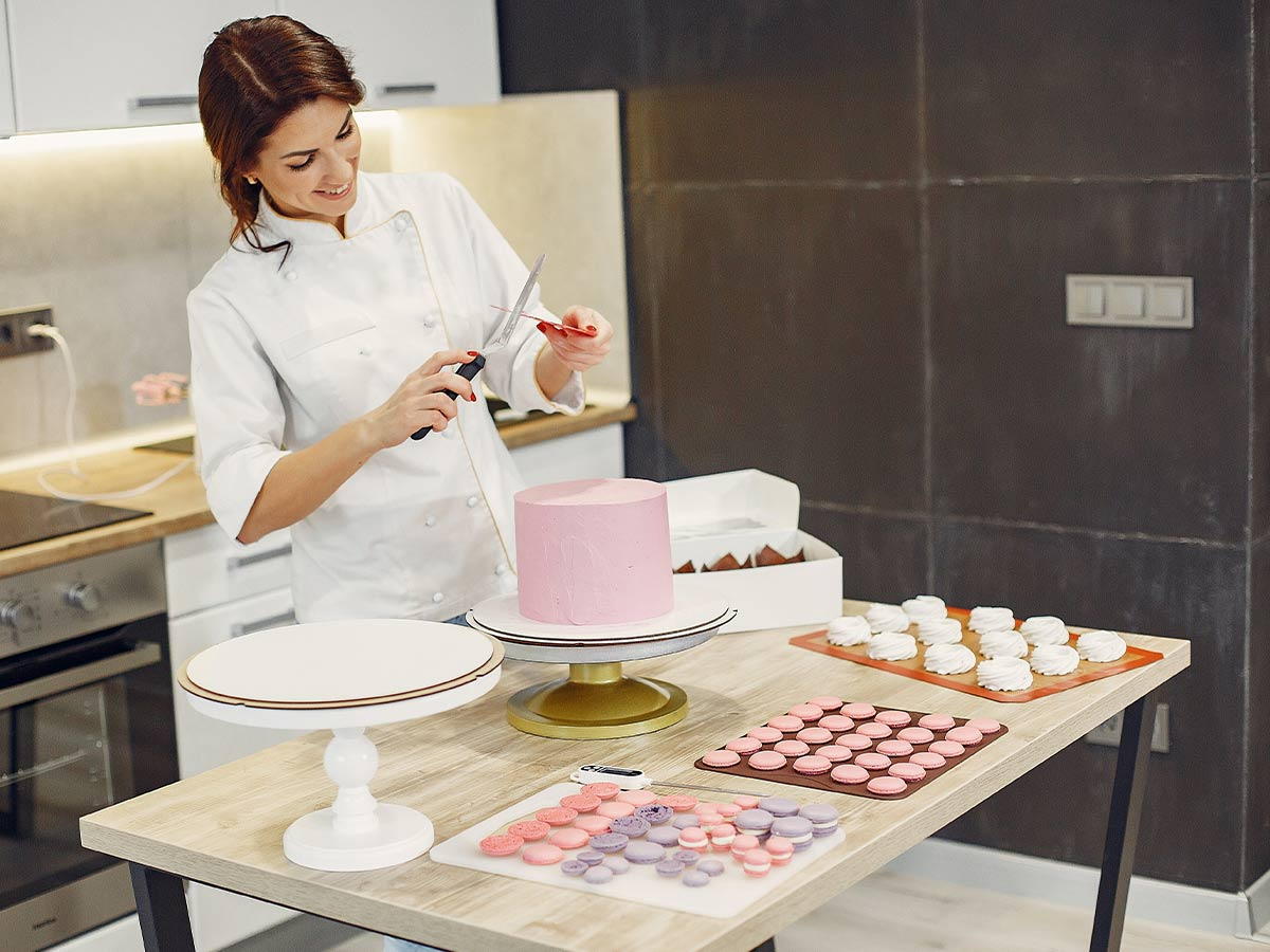 Pastry chef in the kitchen decorating an elaborate pink cake.
