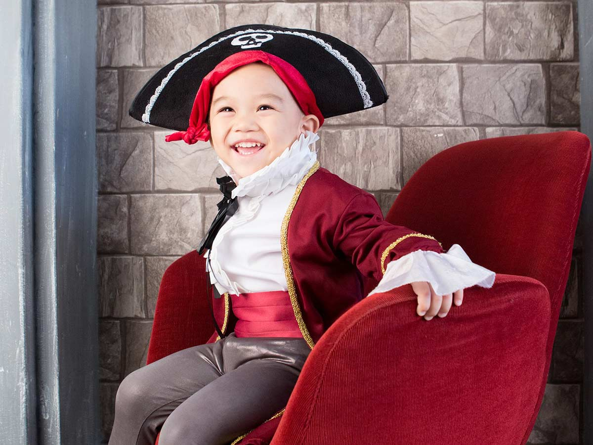 Young boy dressed as a pirate sitting on a red velvet chair.