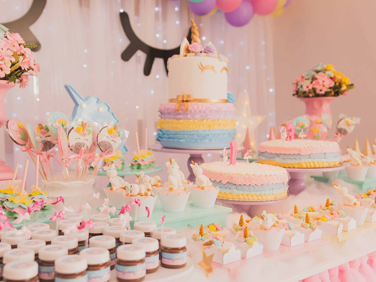 A whole table full of unicorn cakes and cupcakes and unicorn-themed desserts.