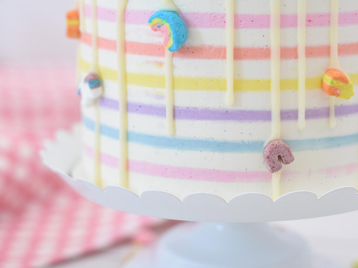 White cake with rainbow striped icing and little rainbow sprinkles stuck round the side.