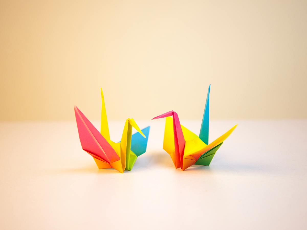 Two multi-coloured origami birds on a table.