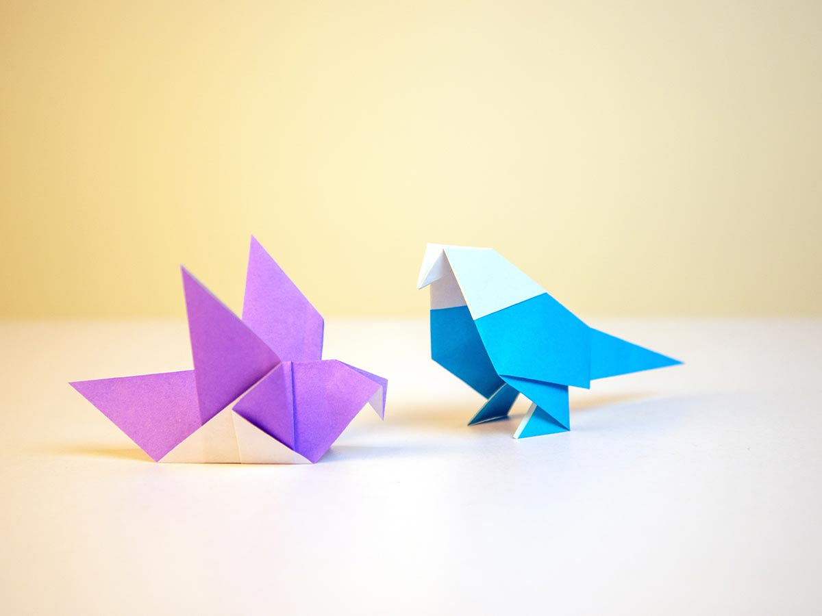 A purple and a blue origami parrot on a white table.