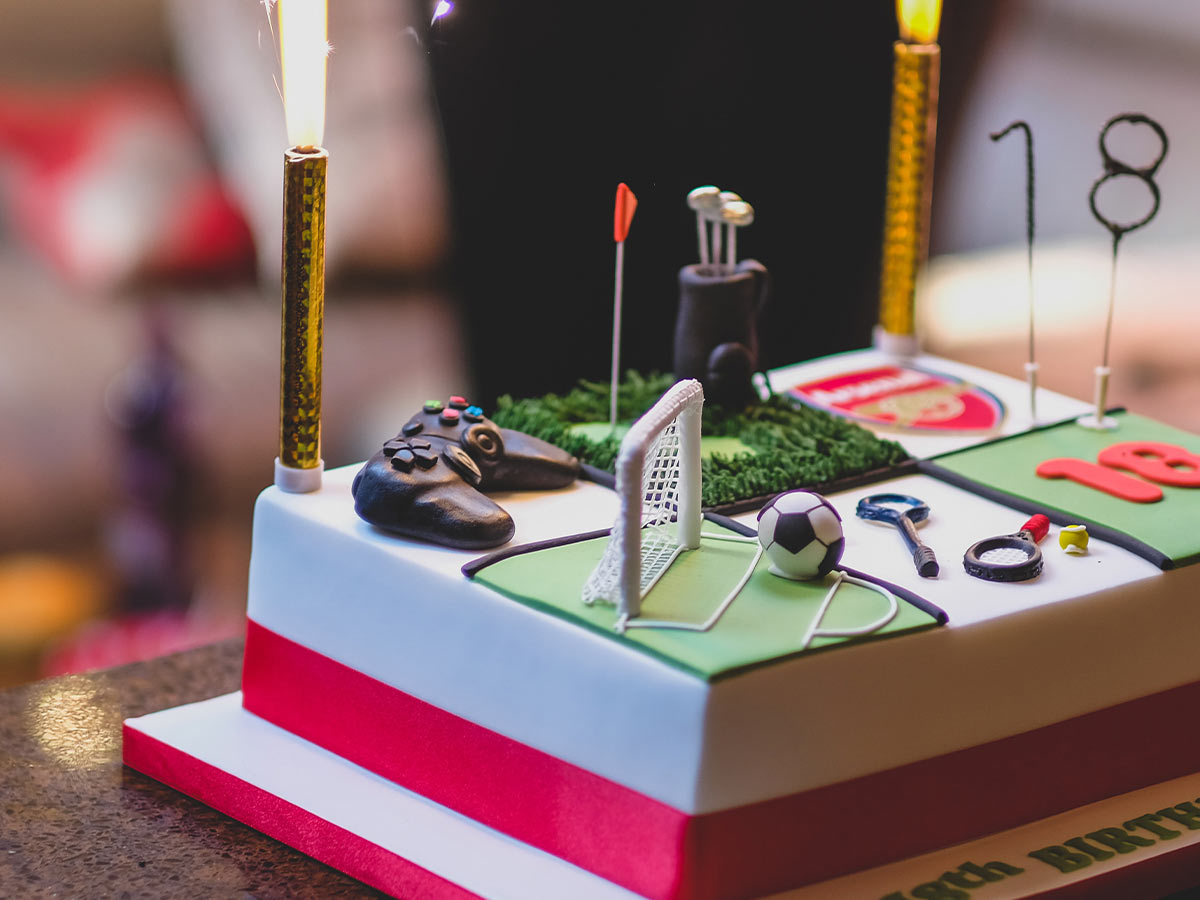 Sports-themed birthday cake with the Arsenal football team logo and a football goal on it.