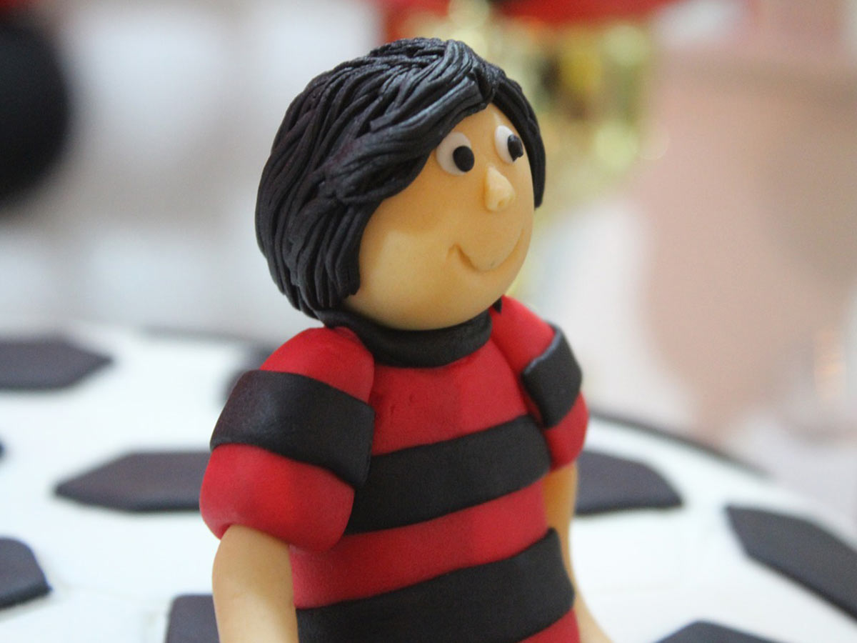 Figure of a boy, made from fondant icing, wearing a striped football shirt.