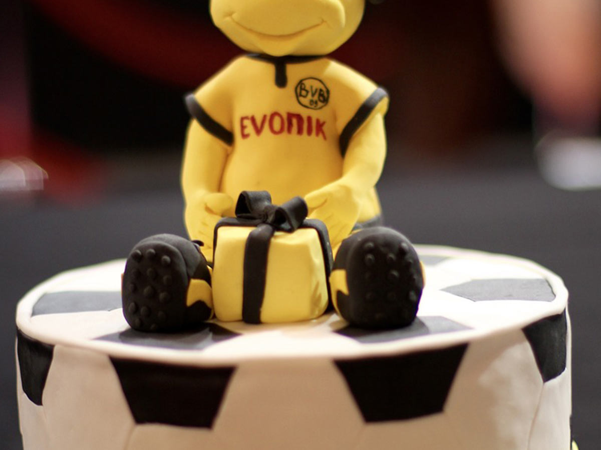 Cake shaped and decorated like a football with an icing figure sat on top wearing yellow football kit.
