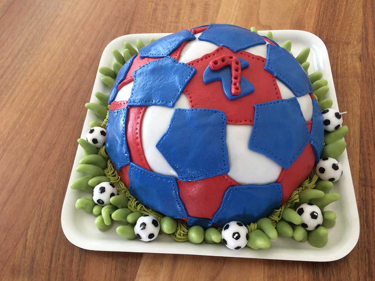 Red and blue football cake with a favourite player's shirt iced onto it.