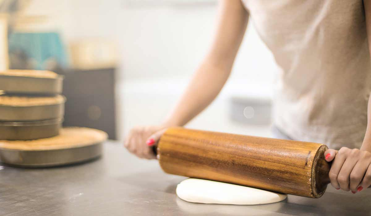 Woman rolling out dough on the worktop using a rolling pin.