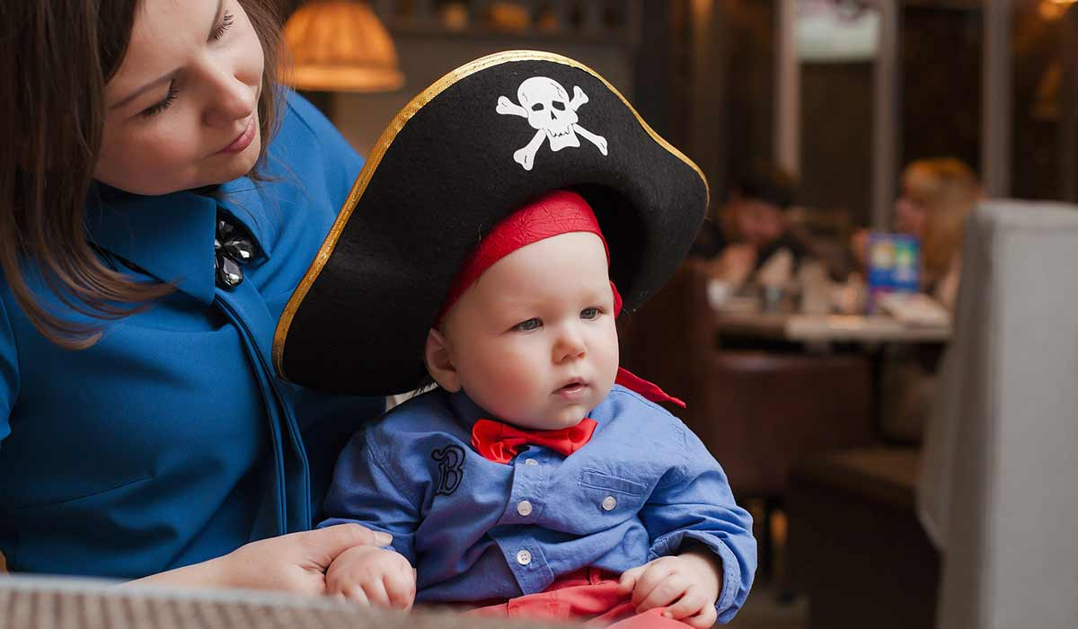 Mum holding baby son who is dressed as a pirate.