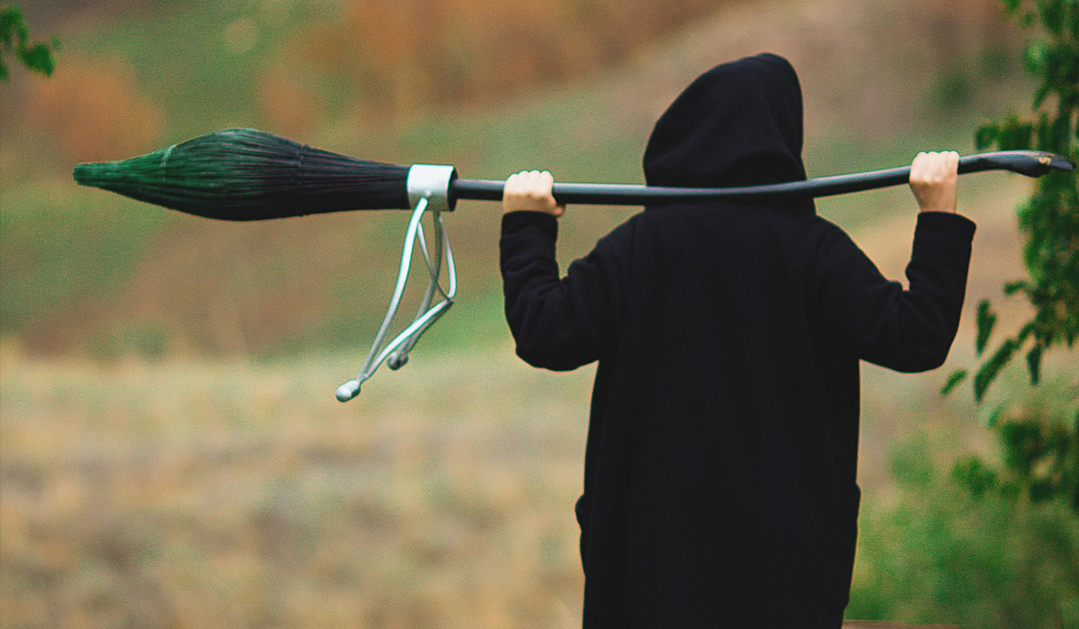 A child wearing a black hooded jacket and holding a broomstick.